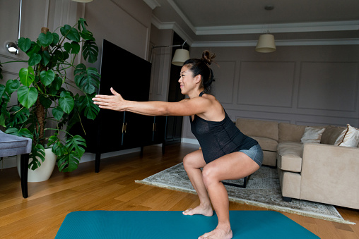 Active pregnant woman holds a squat position while exercising in her home.
