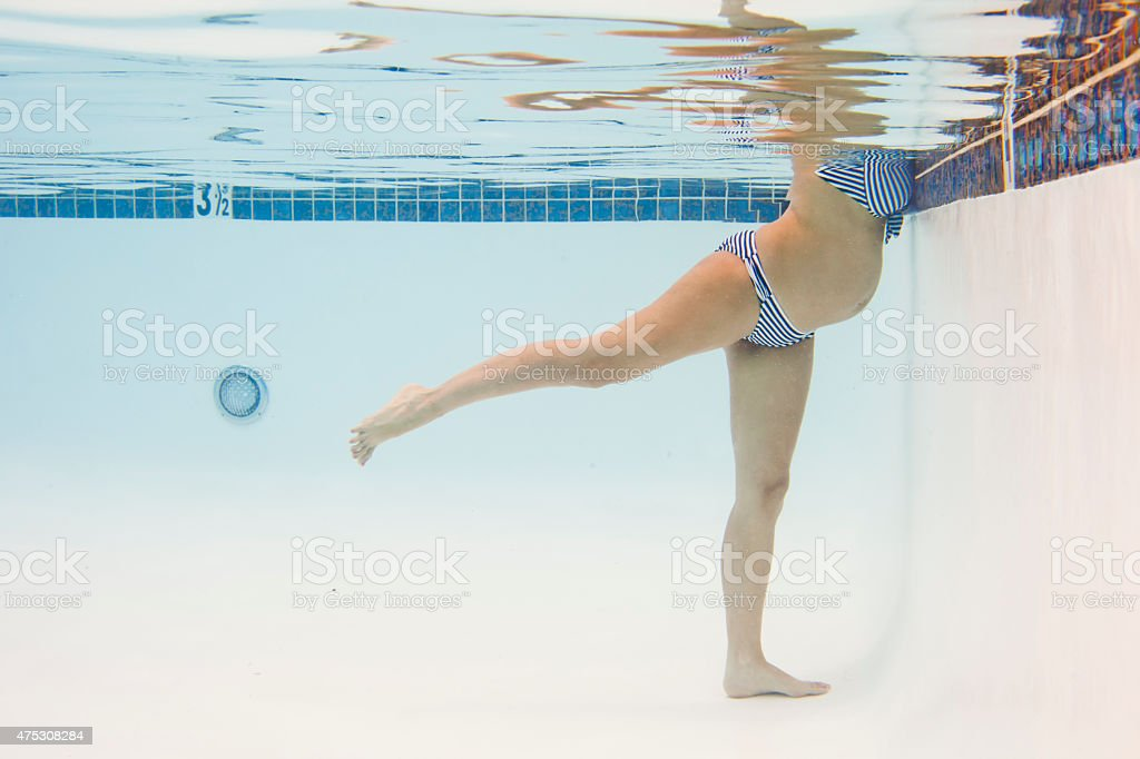Pregnant Woman Exercising in Pool stock photo