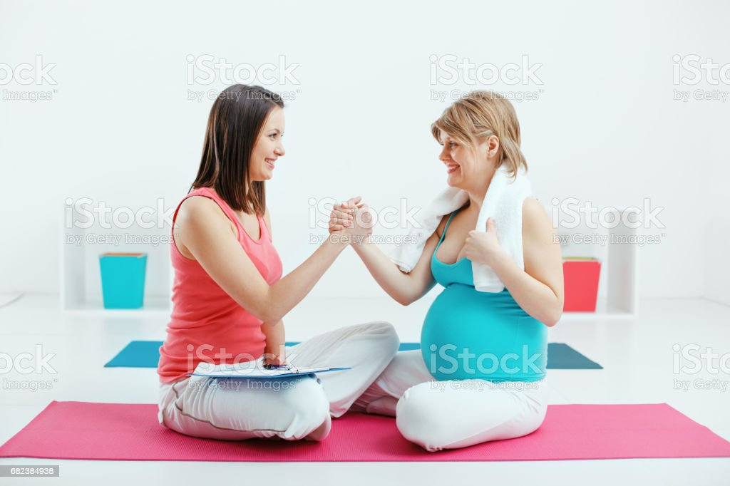 Pregnant Woman Exercising With Her Trainer royalty-free stock photo