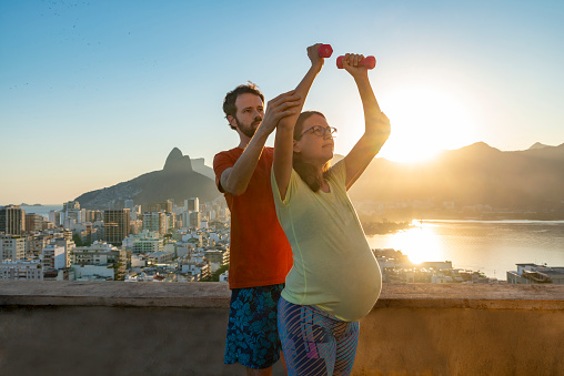 Pregnant woman exercising with instructor on rooftop