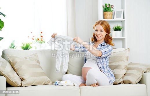 istock pregnant woman expectant mother prepares clothing items for newb 495616694