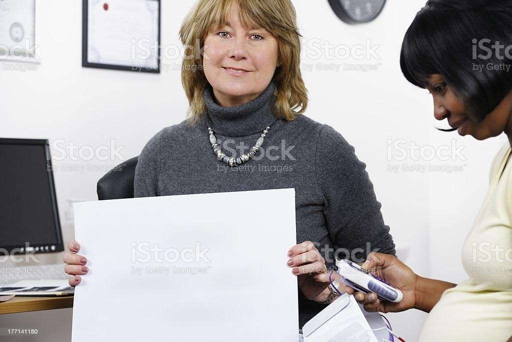 Pregnant Woman Familiarising Herself With Transcutaneous Electrical Nerve Stimulation Machine royalty-free stock photo
