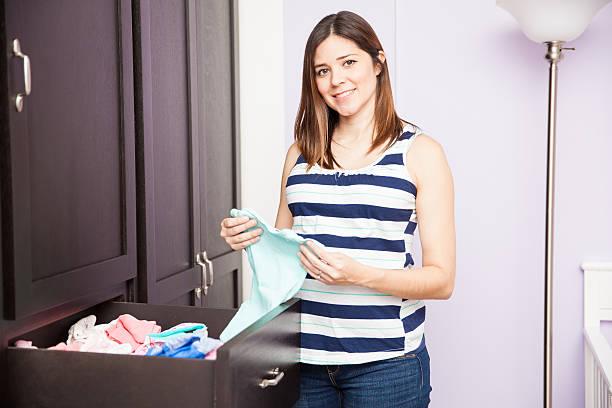 schwangere frau falten-kleidung für babys - mutterkleiderschrank stock-fotos und bilder