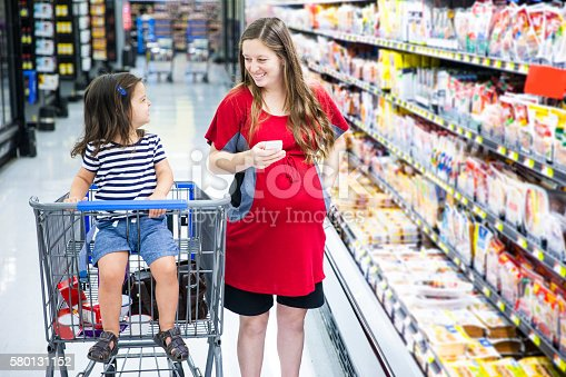 istock Pregnant Woman Grocery Shopping with Daughter 580131152