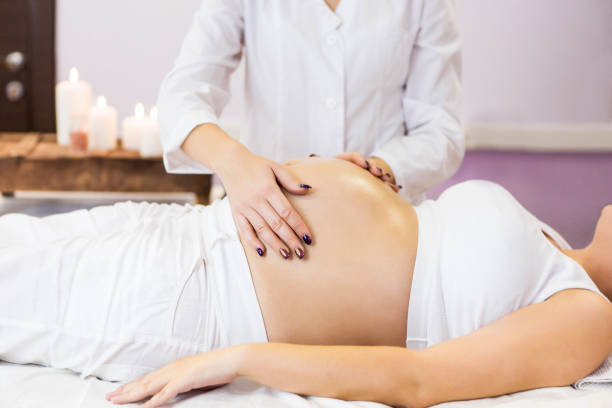 pregnant woman have massage treatment at spa salon - массаж стоковые фото и изображения