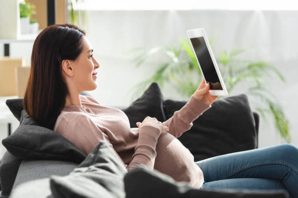 pregnant woman having online consultation with doctor on digital tablet - telemedicine stock pictures, royalty-free photos & images