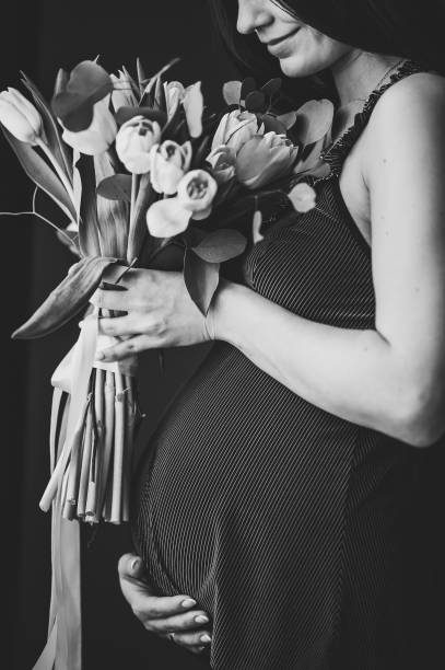 Pregnant woman hold bouquet of flowers in hands, girl embraces a round stomach, belly standing near the window at home. Maternity concept. Close up. nine months. Baby Shower. Black and white photo. stock photo