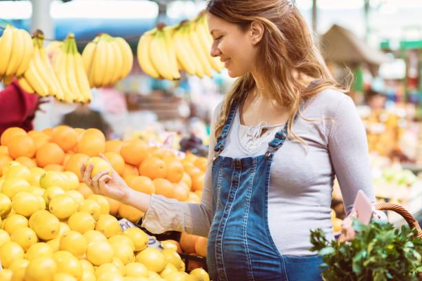 schwangere frau mit einer zitrone auf dem lebensmittelmarkt - latzhose für schwangere stock-fotos und bilder