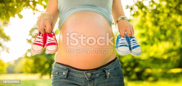 istock Pregnant Woman Holding Baby Shoes 187040993
