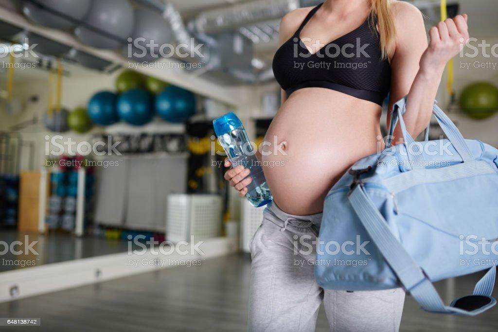 Zwangere vrouw met blauwe zak en bidon op sportschool foto