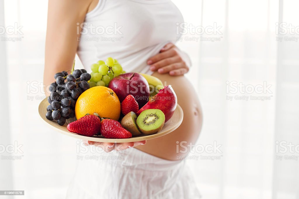 Pregnant woman holding fruit plate stock photo