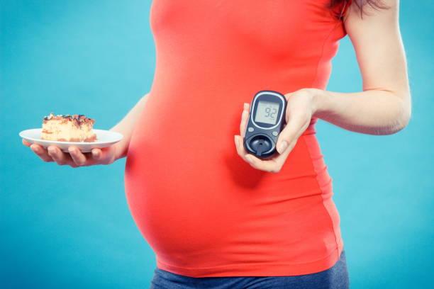 Schwangere Frau mit Blutzuckermessgerät mit guten Ergebnis Zuckergehalt und Stück Käsekuchen, Diabetes und Ernährung während der Schwangerschaft – Foto