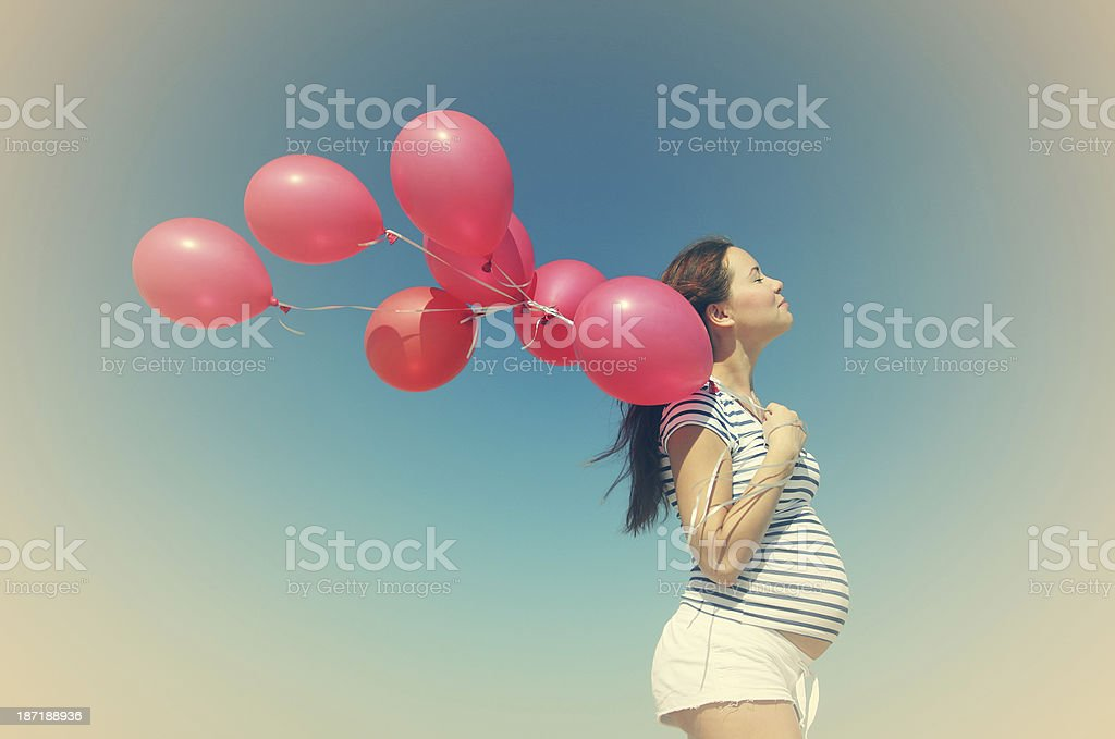 Pregnant woman holding red balloons stock photo
