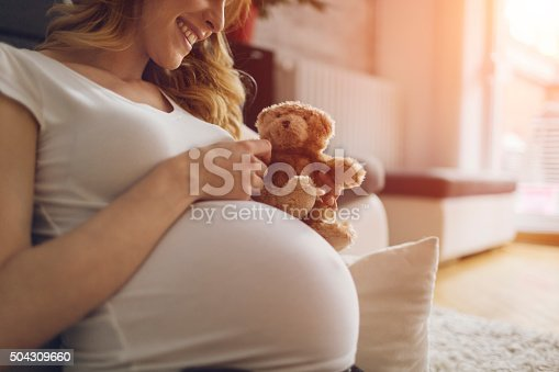 Pregnant Woman Holding Teddy Bear and smiling, sitting on the floor in her living room.  Wearing white T-shirt . Woman has brown curly hair and beautiful smile. Sunlight in background.
