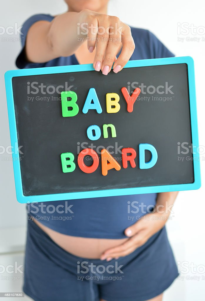 Pregnant woman holds baby on board colored text over belly stock photo