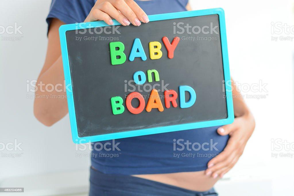 Femme enceinte détient bébé à bord en couleur texte sur la poitrine - Photo