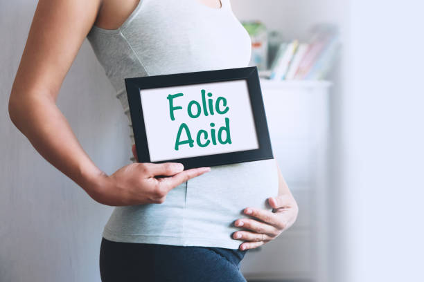 Pregnant woman holds whiteboard with text message - FOLIC ACID. stock photo