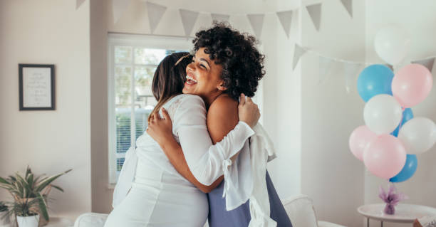 Pregnant Woman Hugging A Friend At Baby Shower Stock Photo