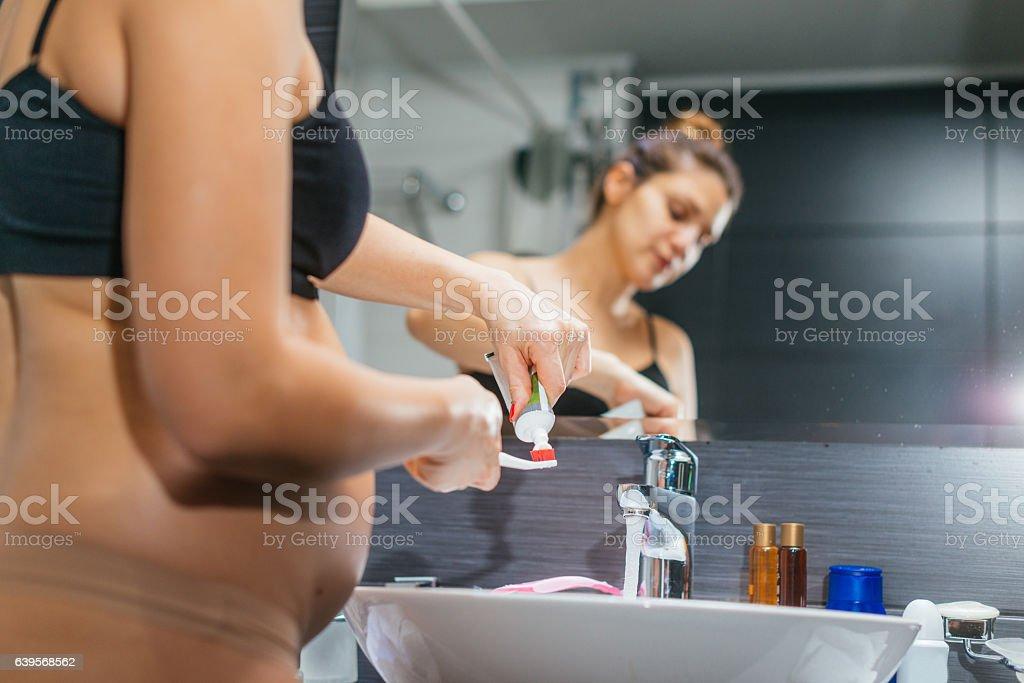 Pregnant woman in bathroom brushing her teeth stock photo
