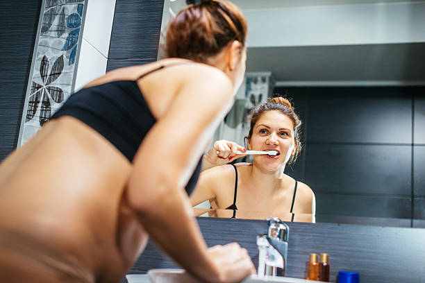 pregnant woman in early 30s brushing her teeth - makeup for pregnant women stock photos and pictures