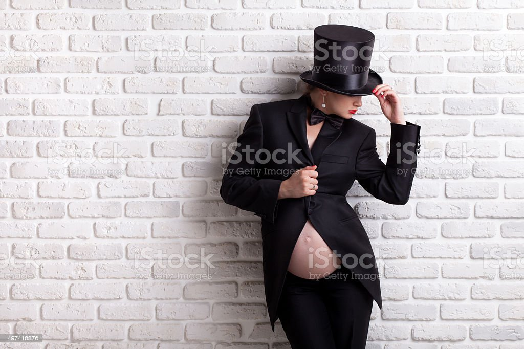 Pregnant woman in evening dress and hat cylinder. stock photo