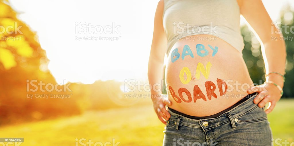 Pregnant Woman In Garden With Text On Belly stock photo
