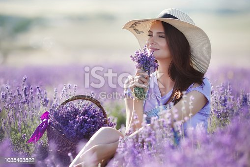 Cute smiling pregnant woman resting in a lavender field. Posing outdoors. Motherhood. Motherhood.Lavender field and a happy pregnant woman.Young beautiful pregnant woman in a hat from the sun on summer meadow in grass on bright Sunny day.