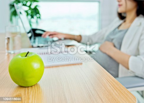 Pregnant woman in office having apple