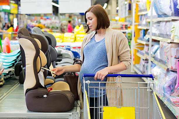 pregnant woman in shop buy car baby seat – Foto