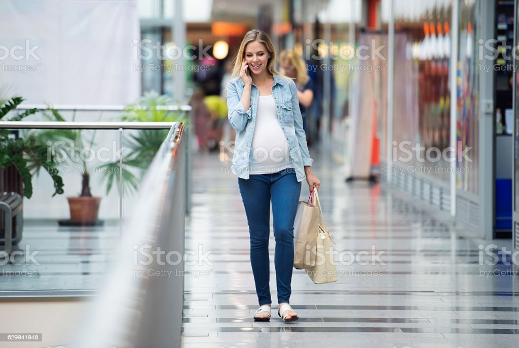 Pregnant woman in shopping center making phone call – Foto