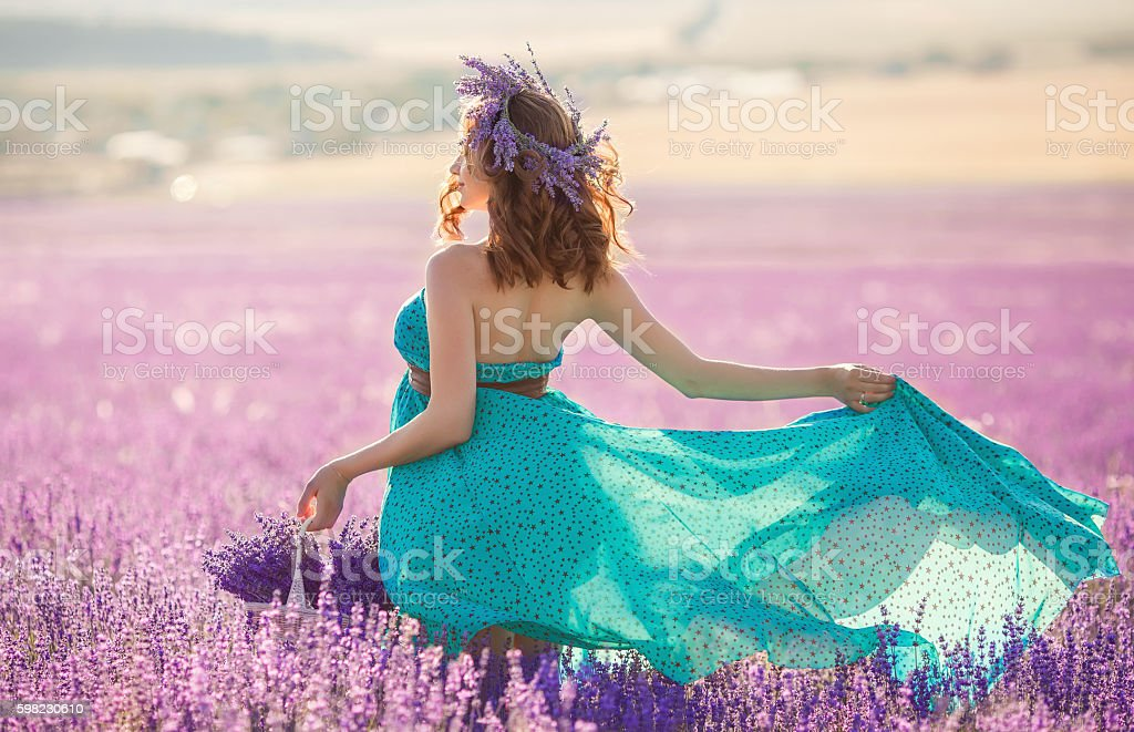 Pregnant woman in turquoise dress on lavender field foto royalty-free
