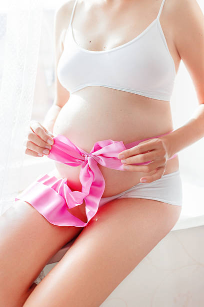 Pregnant woman in white underwear with pink bow on belly. Pregnant woman in white underwear with pink bow on belly. Young woman expecting a baby girl. Cozy happy background in sunny morning. little girls in panties stock pictures, royalty-free photos & images