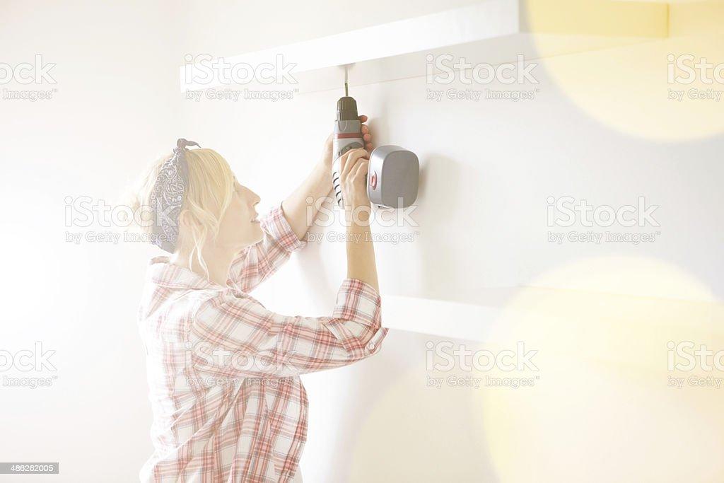 Pregnant woman installing a shelf stock photo