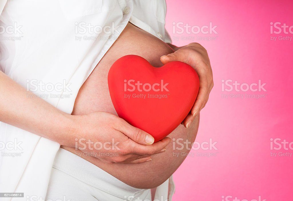 Pregnant woman is holding heart on pink background. Lizenzfreies stock-foto