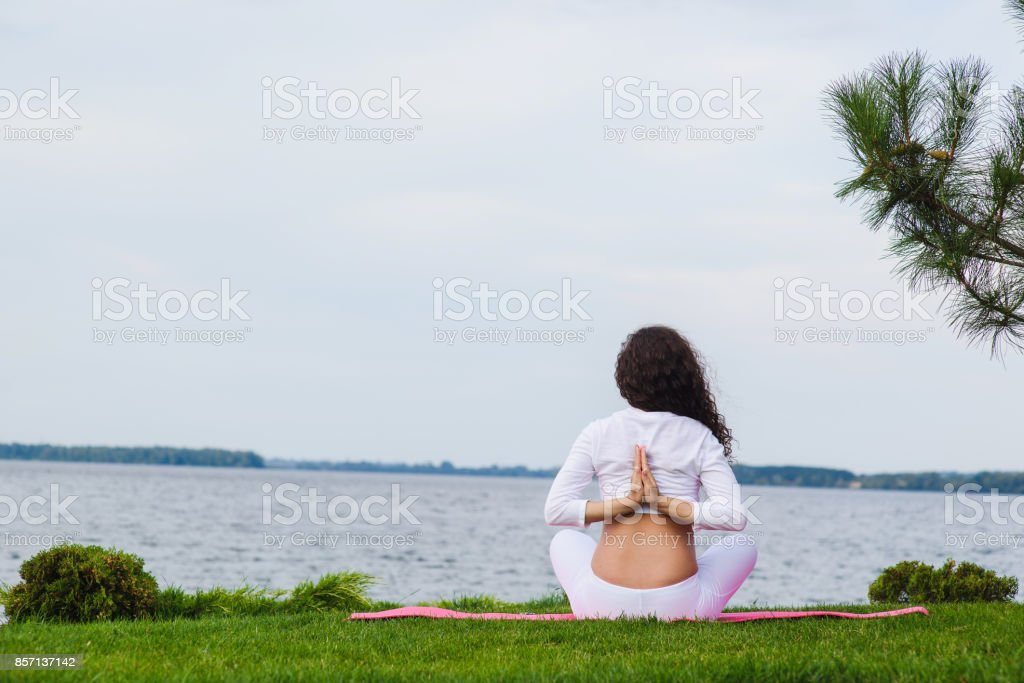 Pregnant woman is practicing yoga beside river stock photo