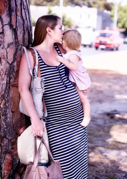 schwangere frau küsst tochter, das sie trägt, ist - kinderhandtaschen stock-fotos und bilder
