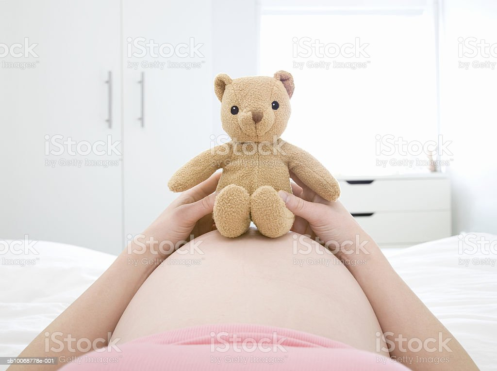 Pregnant woman laying on bed with teddy bear on belly, mid section foto royalty-free