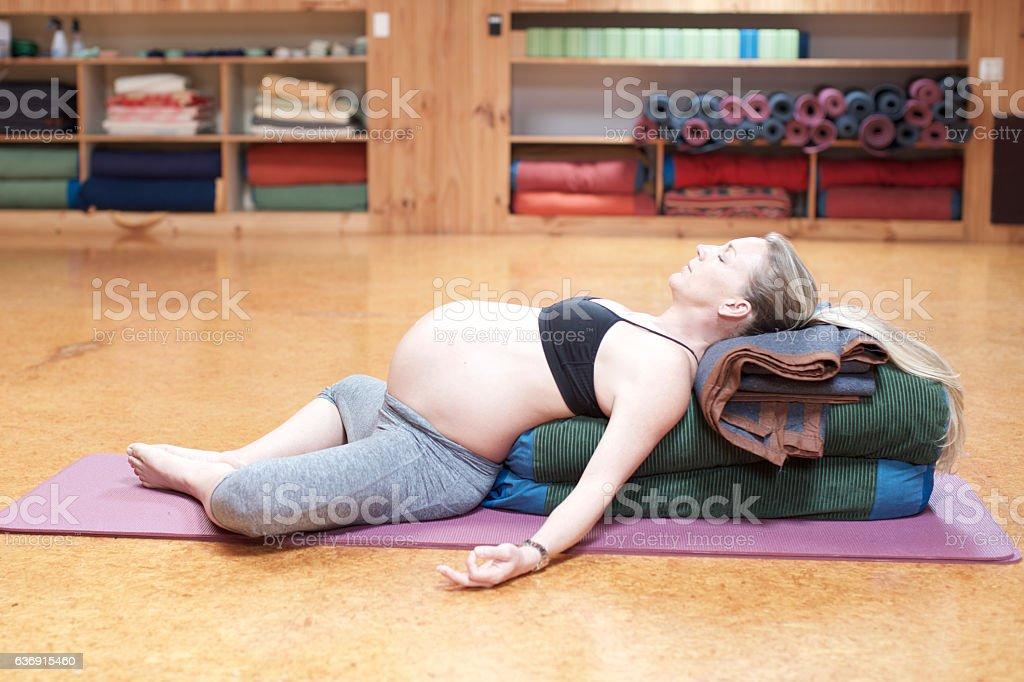 Pregnant woman lies in savasana yoga pose stock photo