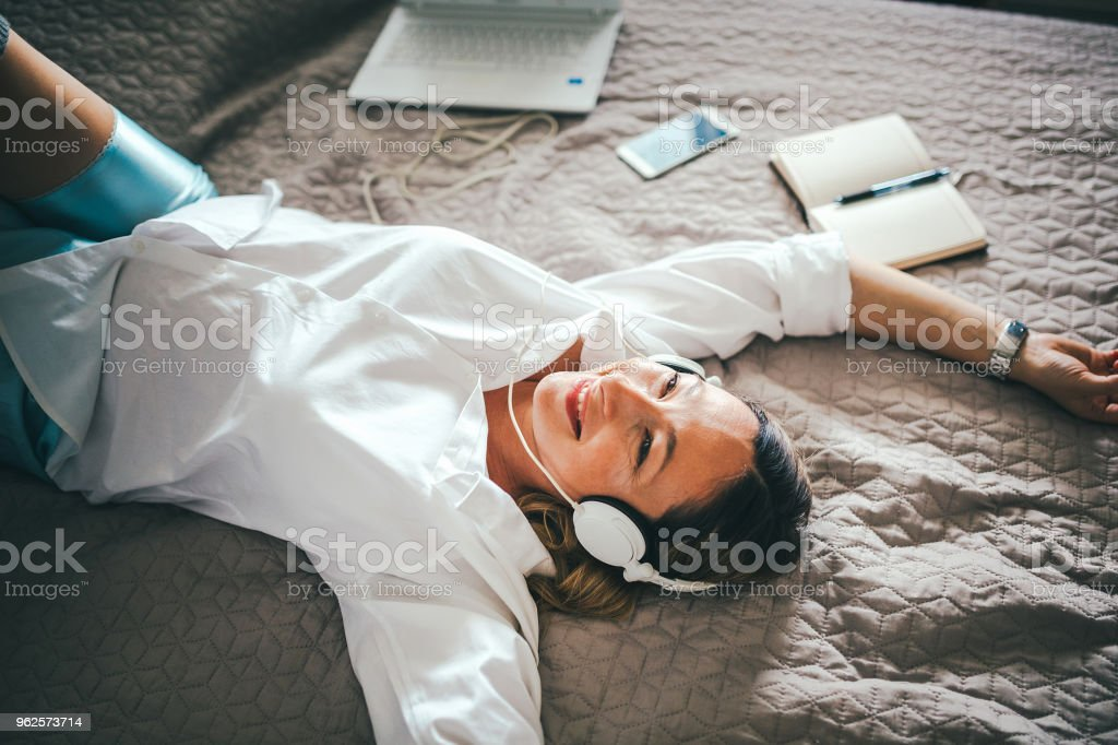 Pregnant woman listening to music in her bedroom stock photo