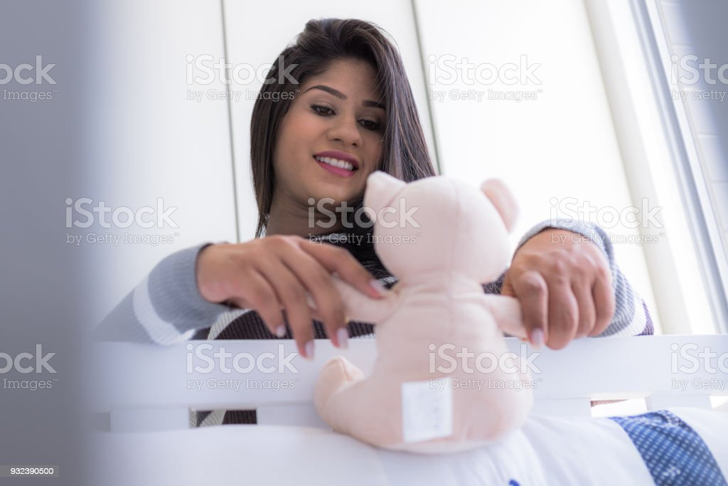 Pregnant woman looking at crib in baby room