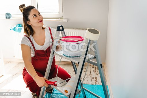 Pregnant woman looking at paint samples on nursery wall