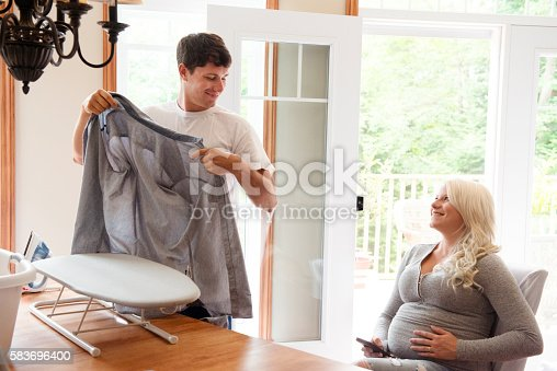 802472024 istock photo Pregnant woman looks tenderly at a man ironing linen 583696400