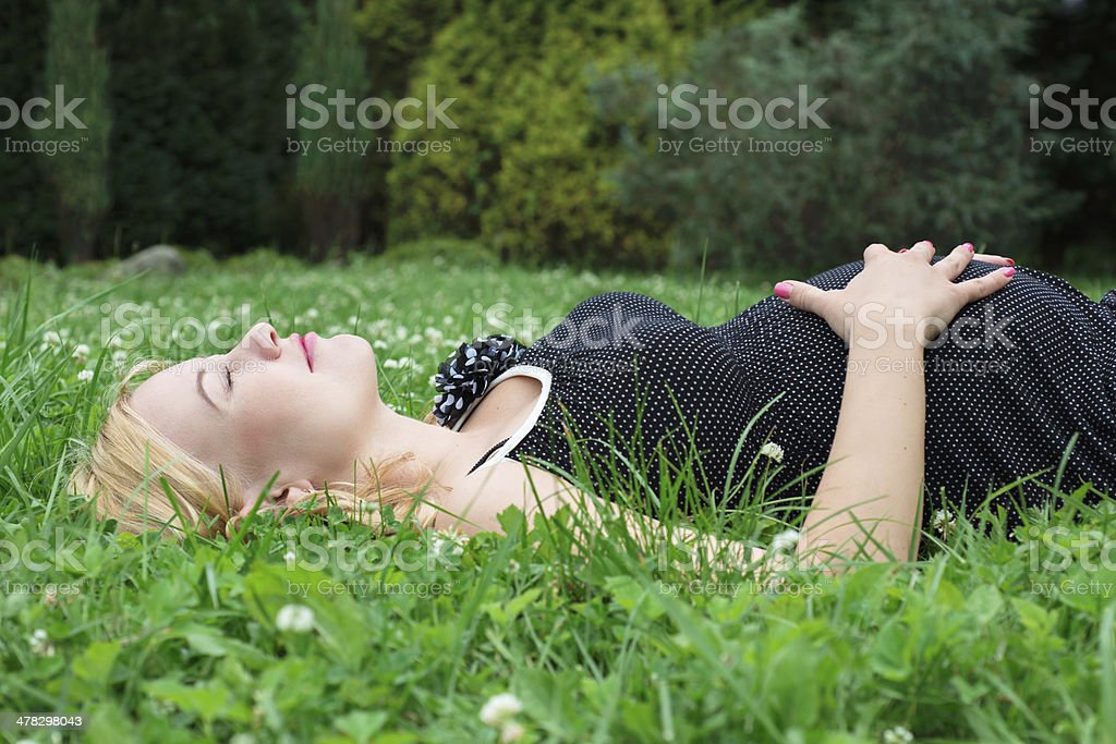 Pregnant woman lying on the grass royalty-free stock photo