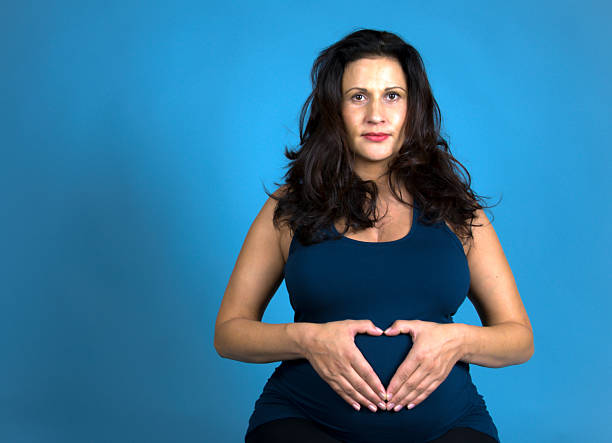 Pregnant woman makes heart on her belly stock photo