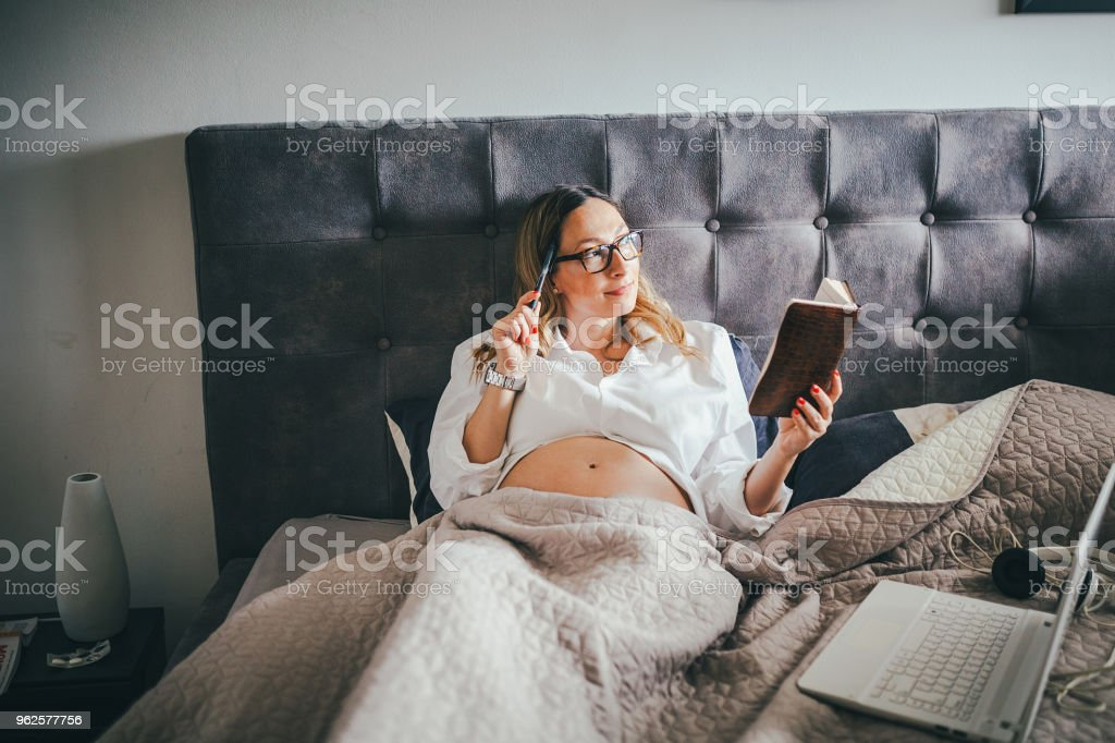 Pregnant woman making a list what to do stock photo