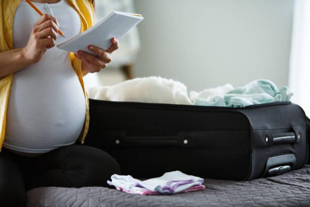 Schwangere Frau, die eine Liste macht, während sie Koffer packt – Foto