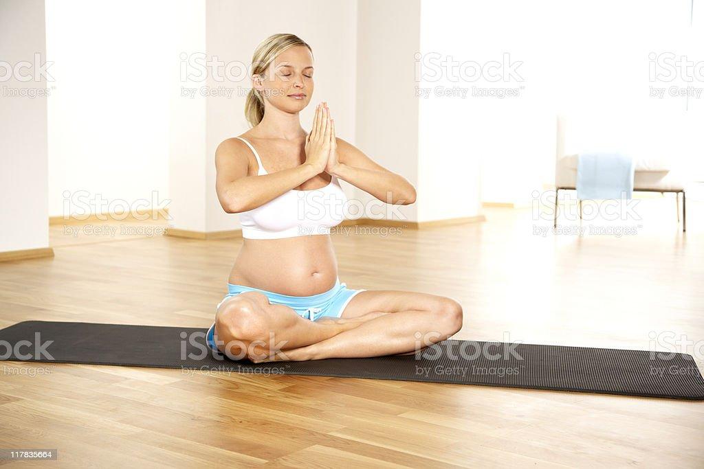 Pregnant woman meditates on black yoga mat royalty-free stock photo