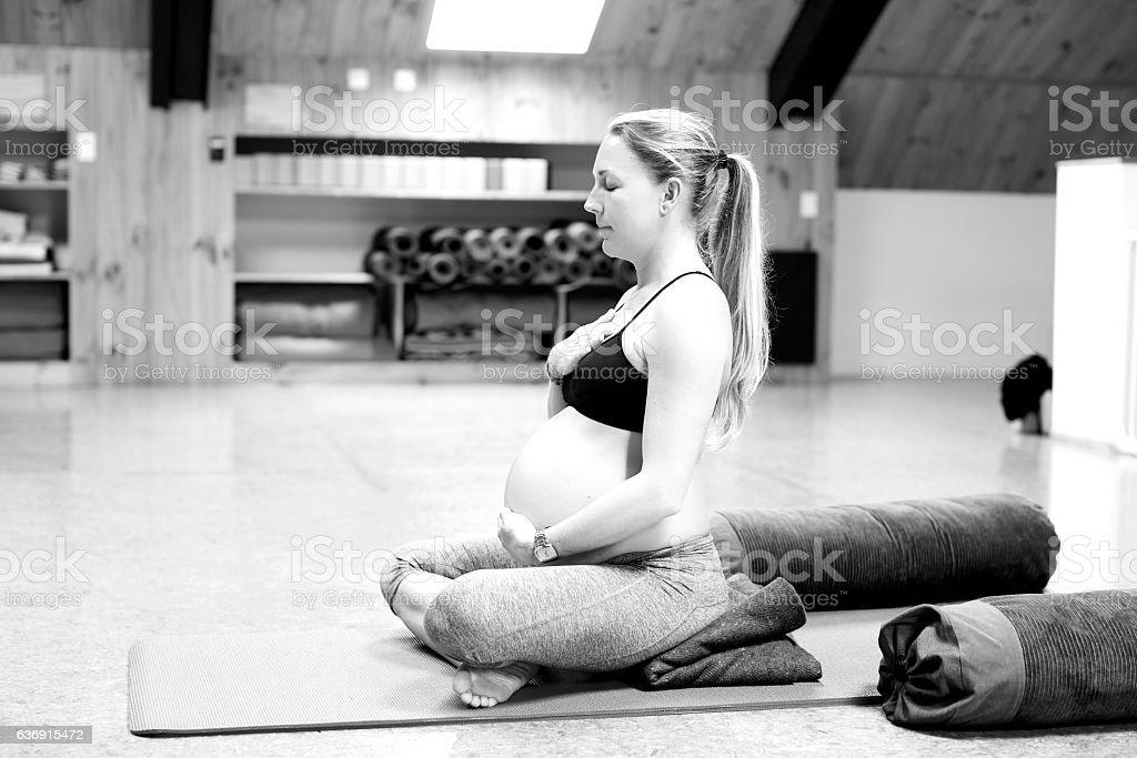 Pregnant woman meditates stock photo