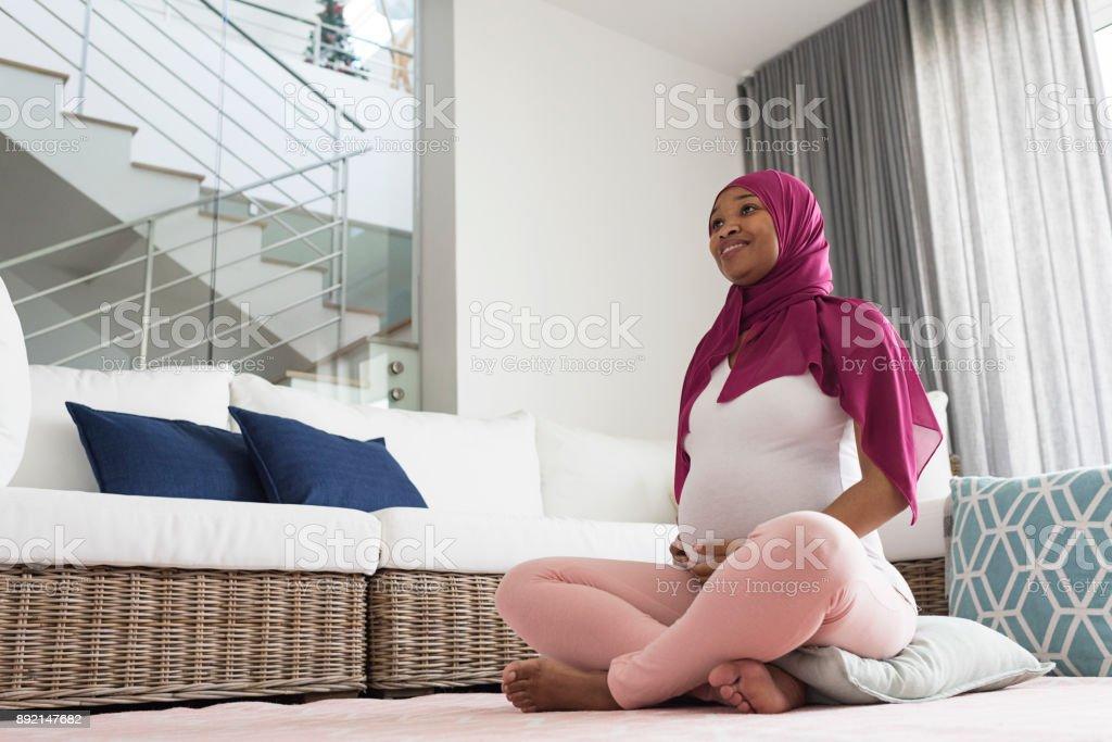 Pregnant woman meditating yoga stock photo