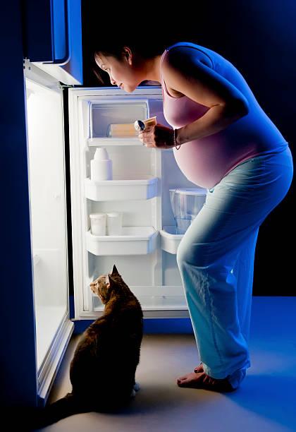 schwangere frau mitternachtssnack - suche katze stock-fotos und bilder